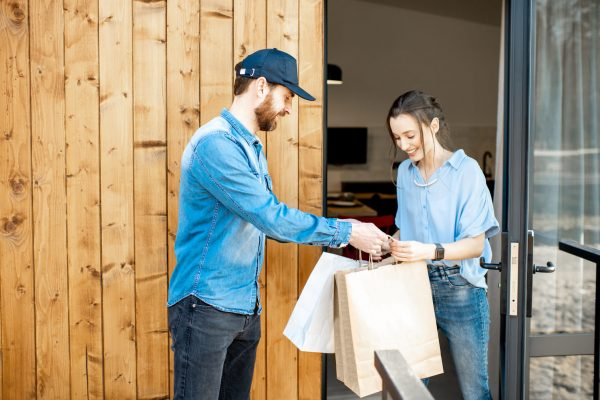 delivery-man-bringing-goods-home-for-a-woman-clien-CG4KECP